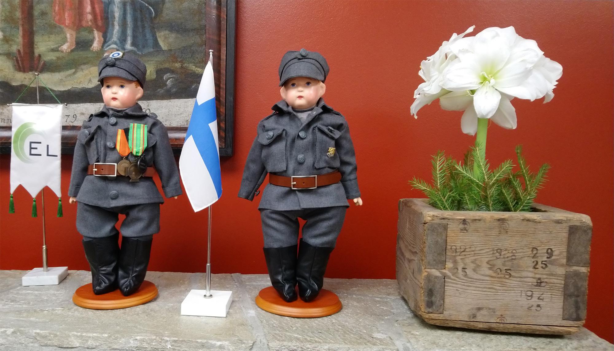 Arja-Linnea Ahosen valmistamat sotilas nuket vasemmalla rinassa hänen isän sota-aikaan saamat kunniamerkit.