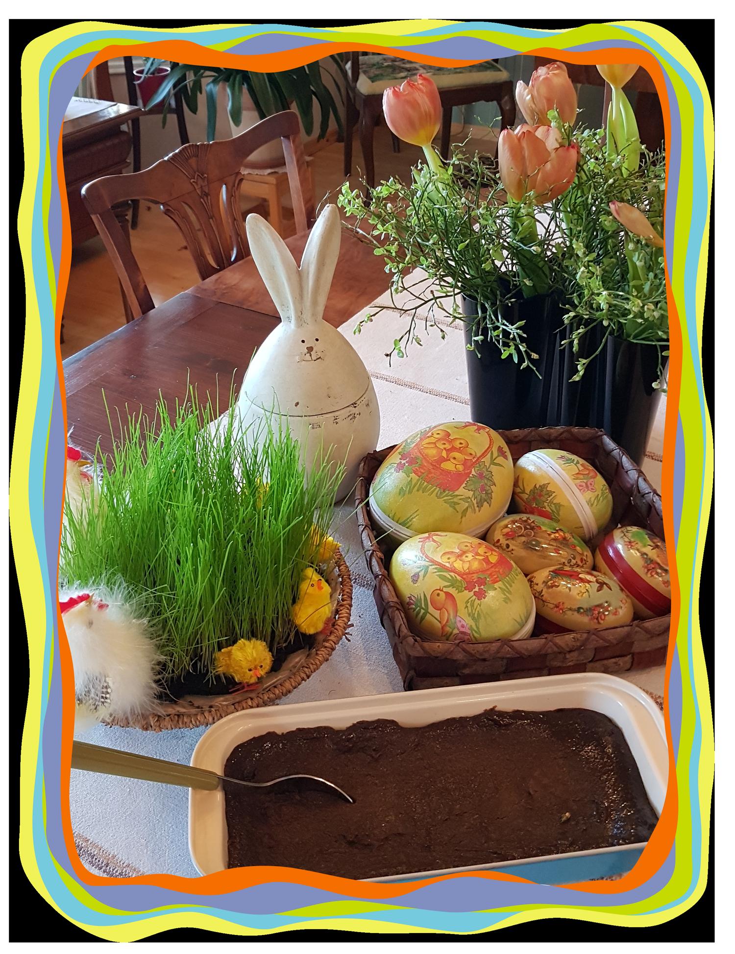Pääsiäinen ruohoa, mämmiä, suklaamunia ja tulppaaneja.